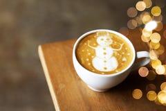 Cappuccino savoureux avec l'art de bonhomme de neige de Noël avec quelques lumières brouillées photographie stock