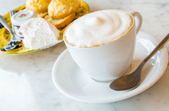 Cappuccino. With scone on the stone table Royalty Free Stock Images