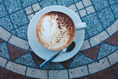 Cappuccino on table. White cup of cappuccino on mosaic table in street cafe stock photo