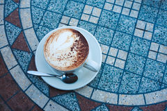 Cappuccino on table. White cup of cappuccino on mosaic table in street cafe royalty free stock photos