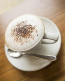 Cappuccino. A Cappuccino on a table background Royalty Free Stock Image