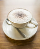 Cappuccino. A Cappuccino on a table background Royalty Free Stock Photo