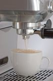 Cappuccino time. Cappuccino machine is pouring coffee to a cap Stock Photos