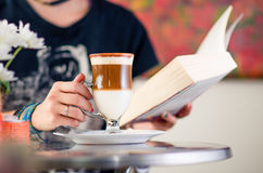 Cappuccino time. Girl holding a cup of cappuccino Royalty Free Stock Image