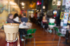 A cappuccino on transparent glass. A cappuccino on on a glass closeup, interior people blurred background Stock Image