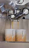 Cappuccino for two. Cappuccino machine is making two caps of coffee Stock Image