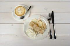 Cappuccino- und Apfelstrudel auf dem Tisch Die Ansicht von der Oberseite Stockfoto