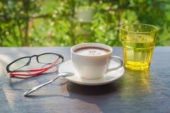 Cappuccino und ein Glas Wasser auf einem Holztisch lizenzfreie stockbilder