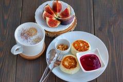Cappuccino- und Hüttenkäsepfannkuchen mit Feigen und Stau zum Frühstück auf hölzernem Hintergrund Stockfotos