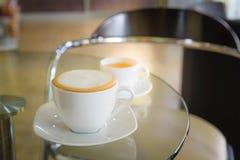 Cappuccino und Tee auf einem Glastisch stockbilder