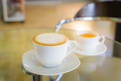 Cappuccino und Tee auf einem Glastisch lizenzfreies stockbild