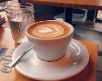 Cappuccino und Wasser im kleinen Weckglas Lizenzfreie Stockfotografie