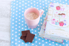 Cappuccino with whipped cream in pastel pink cup. Toned image, coffee, whipped cream, chocolate, pastry book, blue polka dot napkin, composition in pastel colors Stock Photography