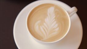 Coffee with whipped cream in a white cup. Cappuccino in a white cup, close-up stock footage