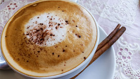 Cappuccino in a white cup on white table. stock photo