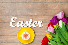 Cappuccino  and word Easter near flowers Royalty Free Stock Images
