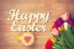 Cappuccino and words Happy Easter near flowers Royalty Free Stock Image