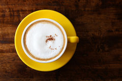 Cappuccino in the yellow cup on the wooden background. Royalty Free Stock Image