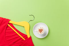 Cappuccino and yellow hanger with red dress Stock Photography