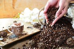 Cappuccinohand mit fallenden Bohnen lizenzfreie stockbilder