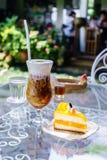 Cappuccinois och den orange kakan i coffee shop arbeta i trädgården Royaltyfri Fotografi
