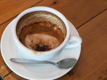 Cappuccinokaffe i den vita koppen på trätabellen, kaffe befläcker af Royaltyfria Foton