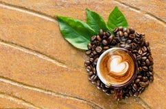 Cappuccinokaffe i en råna med kaffebönan Arkivfoton