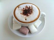 Cappuccinokaffe med marshmallowen som så är läcker på vit Arkivfoton