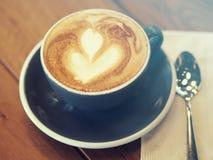 Cappuccinokaffee in der schwarzen Schale auf Holztisch, Weichzeichnung, Summ Stockfotografie