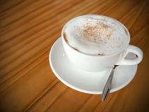 Cappuccinokaffee in der weißen Schale auf Holztisch Lizenzfreie Stockbilder