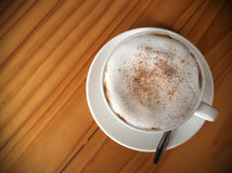 Cappuccinokaffee in der weißen Schale auf Holztisch, Draufsicht Lizenzfreies Stockfoto