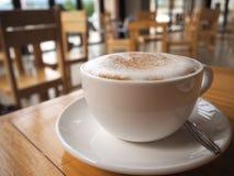 Cappuccinokaffee in der weißen Schale auf Holztisch im Kaffeestubeba Lizenzfreie Stockfotos