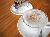 Cappuccinokaffee in der weißen Schale mit Schokoladenkreppkuchen auf Holz Lizenzfreies Stockfoto