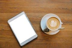 Cappuccinokaffee in einem Becher auf dem Tisch nahe bei einer Tablette mit einem leeren weißen Schirm lizenzfreie stockfotos