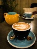 Cappuccinokaffee und gelbe Teekanne mit blauer Schale lizenzfreie stockfotos