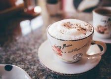 CappuccinoKaffeetasse auf einer Tabelle Lizenzfreie Stockfotos