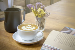 Cappuccinokaffekopp med dekorativa blommor och den öppnade boken Royaltyfri Fotografi