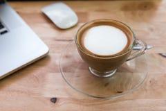 Cappuccinokaffekopp med den bärbar datordatoren och musen royaltyfri bild