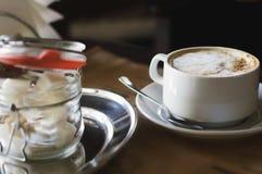 Cappuccinokoffie in een kop en een suiker in een koffie wordt geraffineerd die Close-up royalty-vrije stock afbeelding