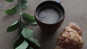 Cappuccinokoffie en croissant op houten achtergrond op de lijst Perfect ontbijt in de ochtend Rustieke stijl stock videobeelden