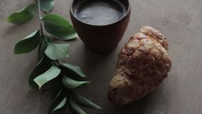 Cappuccinokoffie en croissant op houten achtergrond op de lijst Perfect ontbijt in de ochtend Rustieke stijl stock video