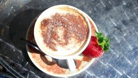 Cappuccinokopp med en jordgubbe stock video