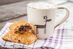 Cappuccinokopp med jul hjortar och muffin med choklad på Royaltyfria Foton