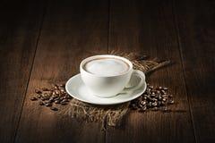 Cappuccinokopp med kaffebönor Arkivfoton