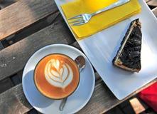 Cappuccinokopp med ostkaka på trätabellen Fotografering för Bildbyråer