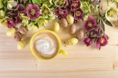 Cappuccinokopp och blommor med påskägg Arkivfoto