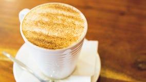 Cappuccinokopp på den bruna trätabellen Royaltyfri Bild