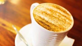 Cappuccinokopp på den bruna trätabellen Royaltyfria Bilder
