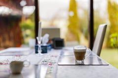Cappuccinokopp på en tabell Arkivfoton
