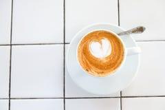 Cappuccinoschale auf mit Ziegeln gedecktem weißem Tabellenhintergrund Schaum wird mit Zimtherzen verziert Kopieren Sie Platz Besc stockfoto